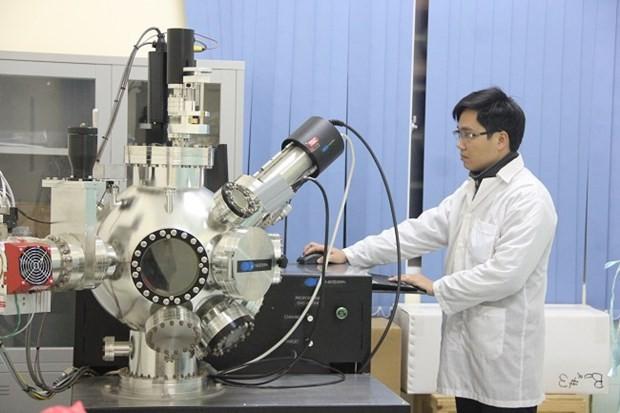 Cán bộ Khoa Vật lý làm việc trên máy tạo màng mỏng bằng chùm xung điện tử. Ảnh: Vietnam+