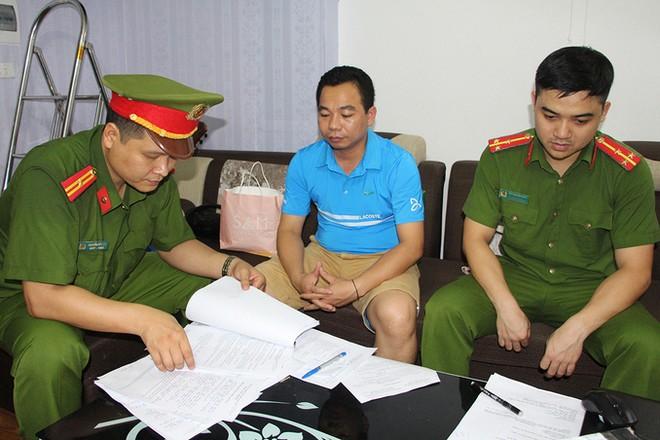 Bị can Kim Văn Bốn (ở giữa) lúc làm việc với công an