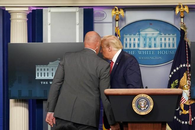 Ông Trump (ảnh phải) được nhân viên mật vụ hộ tống rời khỏi phòng họp báo
