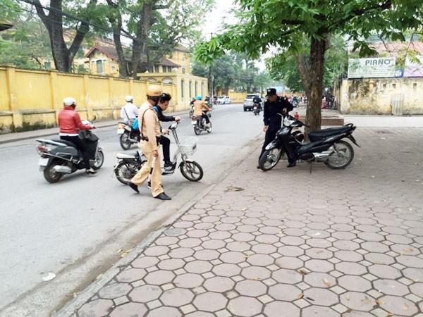 Bắt đầu xử phạt học sinh ngồi trên xe đạp điện, xe máy không đội mũ bảo hiểm ảnh 1