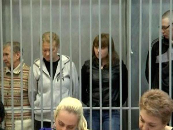 Các bị cáo Evdokia, Olga, Elena và Sergei trong phòng cách ly tại tòa (từ trái sang)