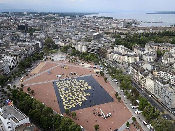 """Tấm biểu ngữ khổng lồ được trải trên mặt đất tại Geneva nêu câu hỏi: """"Bạn sẽ làm gì nếu thu nhập của bạn được bảo đảm suốt đời?"""""""