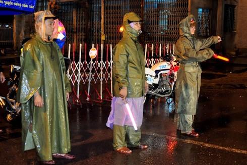 Cán bộ, chiến sĩ Trạm Cảnh sát giao thông Tuy Phước dầm mưa phân luồng, điều tiết giao thông tại những điểm ngập lụt trên tuyến quốc lộ 1, đoạn qua phường Trần Quang Diệu, TP Quy Nhơn, tỉnh Bình Định