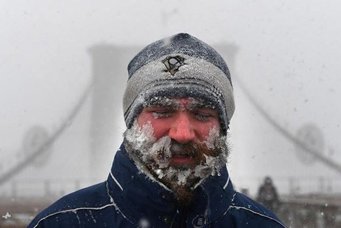 Người đàn ông đi bộ qua cầu Brooklyn ở thành phố New York bị băng tuyết phủ kín khuôn mặt