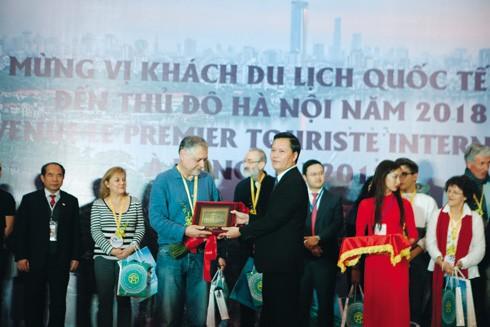 Ông Trần Đức Hải, Giám đốc Sở Du lịch Hà Nội tặng quà du khách quốc tế đầu tiên đến Hà Nội năm 2018