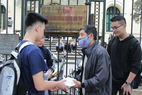 Các tình nguyện viên trong nhóm Hanoi Food Rescue trao thức ăn cho các bệnh nhân nghèo tại bệnh viện K Hà Nội