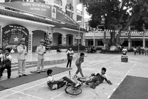 Thượng úy Hoàng Mạnh Cường (bên phải) tham gia tuyên truyền an toàn giao thông cho học sinh tiểu học