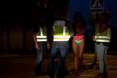 Cảnh sát chống buôn người tiếp cận với một phụ nữ trên đường phố Colonia Marconi, Madrid