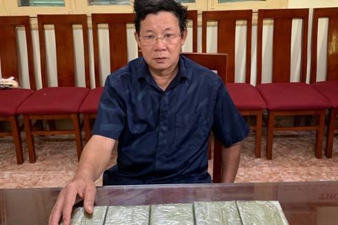 Đối tượng Hồ Xuân Long và 5 bánh heroin mà y chuyển từ Nghệ An ra Hà Nội