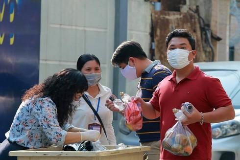 Người dân ở phố Trúc Bạch (quận Ba Đình, Hà Nội) tiếp nhận nhu yếu phẩm từ chính quyền địa phương