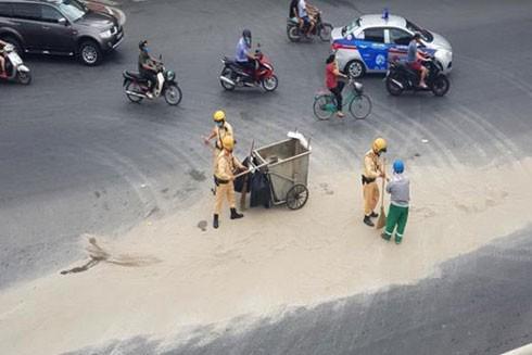 Lực lượng chức năng cùng nhân viên vệ sinh môi trường dọn cát rơi vãi trên đường, nhằm đảm bảo an toàn giao thông