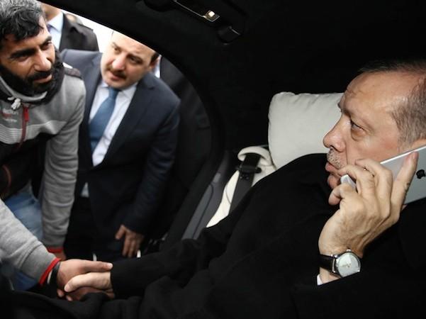 Tổng thống Erdogan một tay cầm điện thoại, một tay bắt tay người đàn ông định tự tử