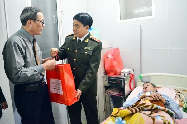 Đại diện gia đình đồng chí Phạm Hồng Liên nhận quà chúc Tết từ Thiếu tướng Nguyễn Đức Chung, Giám đốc CATP Hà Nội
