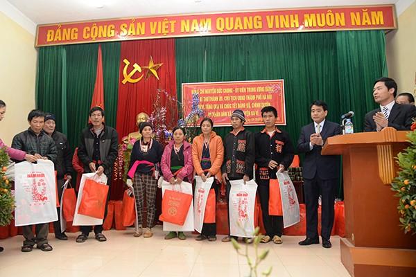 Chủ tịch UBND TP.Hà Nội Nguyễn Đức Chung (thứ 2 từ phải qua) tặng quà của UBND TP tới các hộ nghèo xã Ba Vì (huyện Ba Vì)