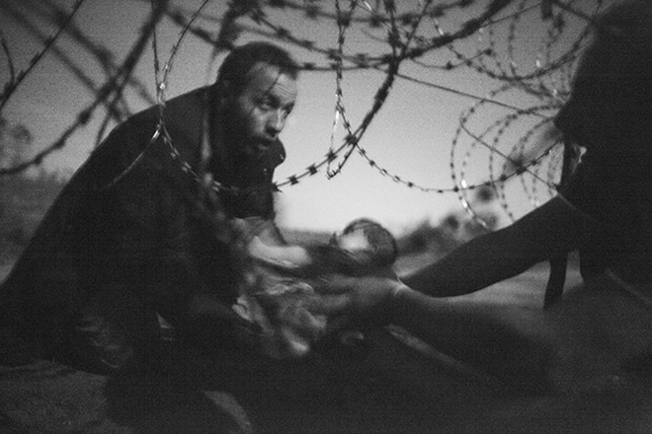 Ấn tượng, ám ảnh với bức ảnh người tị nạn đưa con qua hàng rào thép gai ảnh 1