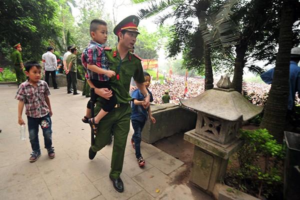 Lực lượng Công an bế các em bé thoát khỏi biển người chen lấn tại đền Hùng ảnh 7
