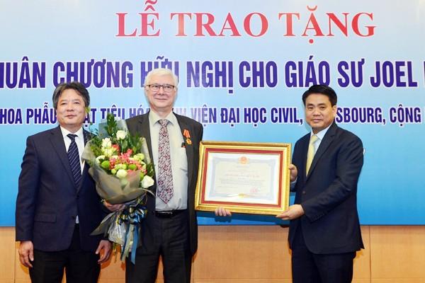Thừa uỷ quyền của Chủ tịch nước CHXHCN Việt Nam, Chủ tịch UBND TP Nguyễn Đức Chung đã trao Huân chương Hữu nghị cho GS. Joel Leroy