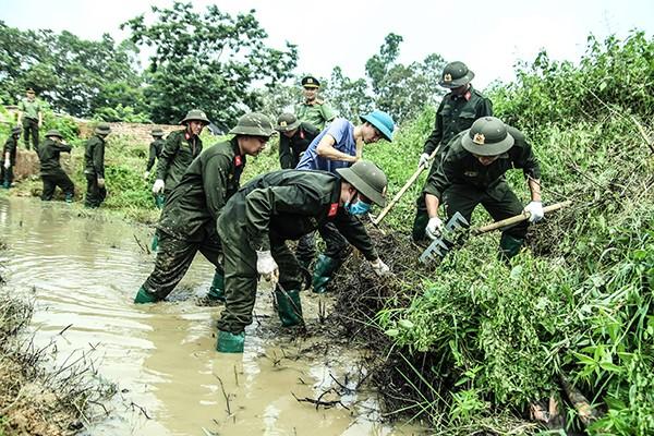Thanh niên Công an khai thông kênh mương phục vụ công tác trồng trọt của nhân dân ở xã Minh Trí, Sóc Sơn