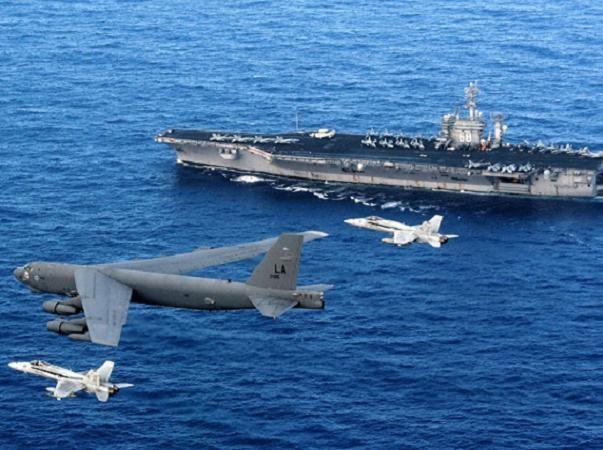 Máy bay ném bom chiến lược B-52, được 2 tiêm kích hạm F/A-18 Hornet hộ tống, bay trên đầu tàu sân bay hạt nhân CVN-68 USS Nimitz