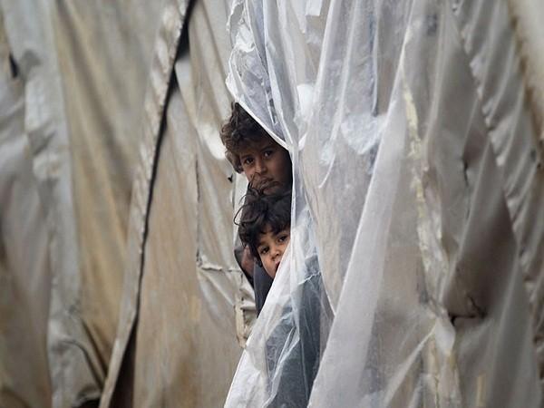 Từ một căn lều tạm bợ ở trại Jerijaz, hai bé trai ngó ra ngoài khi người lạ tới.