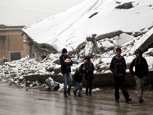 Các thanh niên đi bộ ở quanh khu đổ nát bị tuyết trắng bao phủ, tại khu vực do lực lượng nổi dậy chiếm đóng ở thị trấn Maaret al-Numan, tỉnh Idlib.