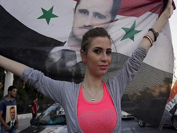 Công dân Syria mang cờ của Syria có chân dung Tổng thống Bashar al-Assad