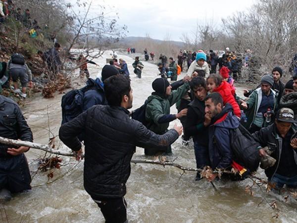 Những người di cư đang vượt qua một con sông gần biên giới Hy Lạp - Macedonia ngày 14-3