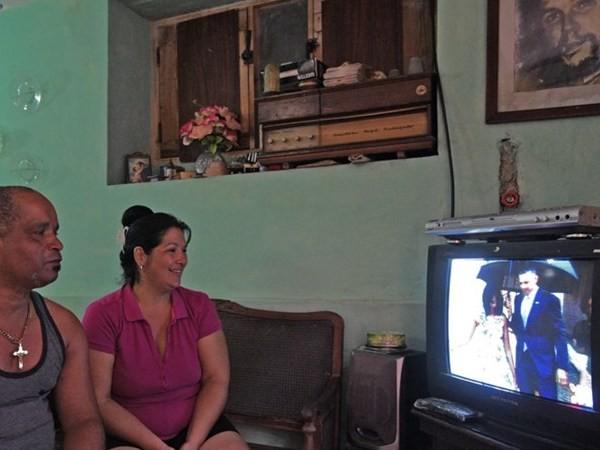 Hai vợ chồng sinh sống ở La Habana theo dõi ti vi đang chiếu bản tin nói về chuyến thăm lịch sử Cuba của Tổng thống Mỹ Obama.