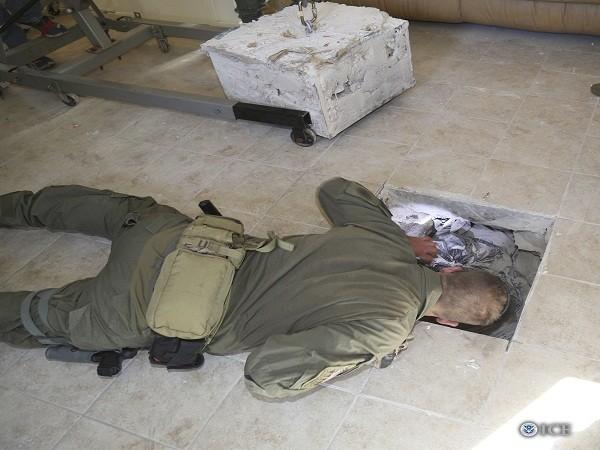Một cảnh sát thuộc đội phản ứng nhanh Cục điều tra an ninh Mỹ đang nhìn xuống đường hầm trong khi tiến hành điều tra vụ việc.