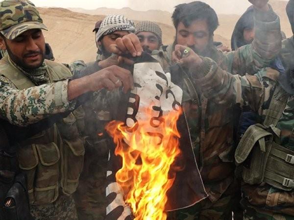 """Lực lượng dân quân """"Chim ưng sa mạc"""" đốt một lá cờ của IS, sau khi họ gỡ xuống khỏi thành trì của những kẻ khủng bố ở Palmyra."""