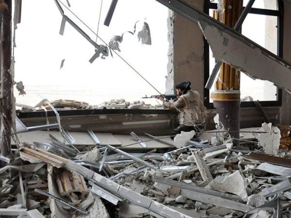 Một binh sĩ của quân đội chính phủ Syria chiếm vị trí bên trong một lâu đài bị hư hỏng, ở lối vào Palmyra, miền trung Syria.