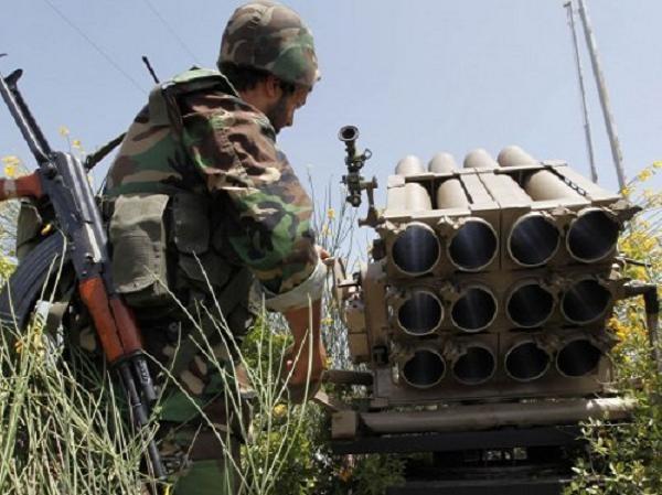 Tay súng Hezbollah đứng bên một bệ phóng rocket đa nòng