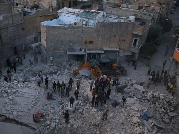 Lực lượng chức năng có mặt tại hiện trường sau một vụ không kích ở Aleppo