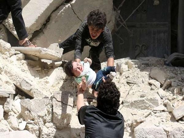 Một em bé được đưa ra khỏi tòa nhà bị phá hủy sau một trận không kích ở Syria