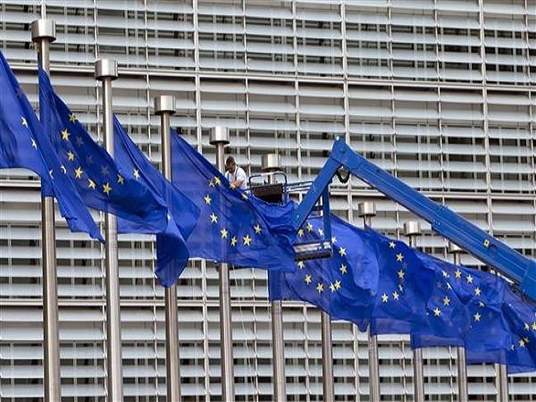 Một người công nhân đang chỉnh lại cờ của EU phía trước trụ sở của khối ở Brussels
