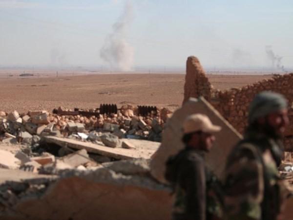 Khói bốc lên từ phía xa khi các thành viên SDF lục soát hiện trường đổ nát ở phía bắc thành phố Raqqa