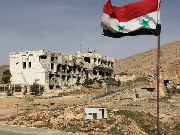 Cờ Syria được cắm gần tòa nhà bị phá nát ở thị trấn Maaloula, cách Damascus 55km