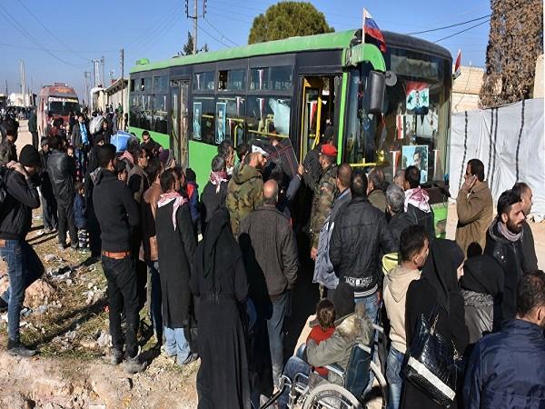 Người dân đang xếp hàng chờ lên xe buýt của lực lượng chính phủ ở làng Aziza, ngoại ô thành phố Aleppo, ngày 9-12-2016