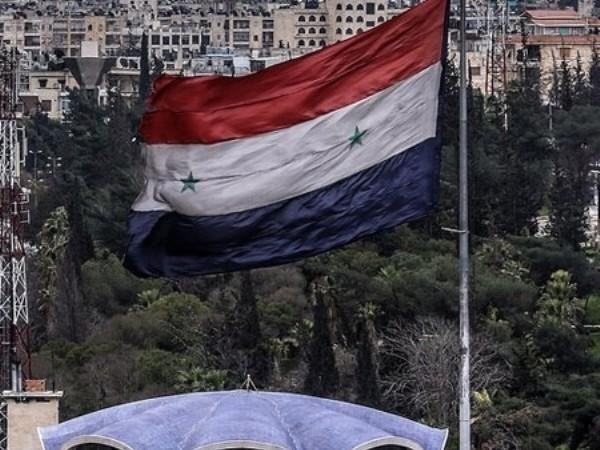 Cờ Syria được cắm trên nóc của một tòa nhà ở Aleppo, khu vực vừa được lực lượng vũ trang Damascus giải phóng khỏi tay phiến quân