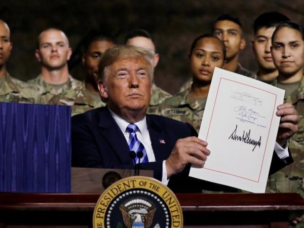 Tổng thống Donald Trump giơ cao văn bản luật quốc phòng vừa ký trước các quân nhân Mỹ tại căn cứ Fort Drum, New York, ngày 13-8-2018