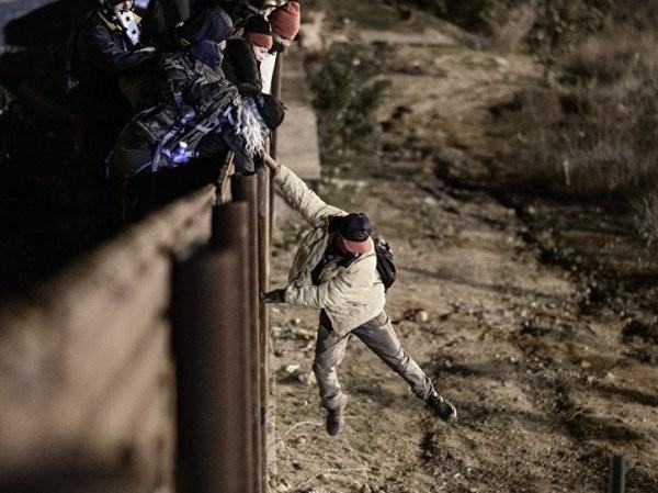 Một người di cư nhảy qua hàng rào biên giới để vào Mỹ, ngày 1-1-2019
