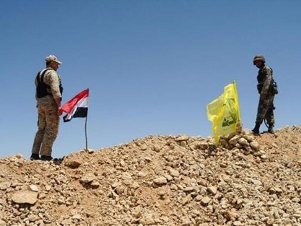 Cờ của quân đội Syria và cờ của lực lượng Hezbollah được cắm trên một ngọn đồi ở Aleppo