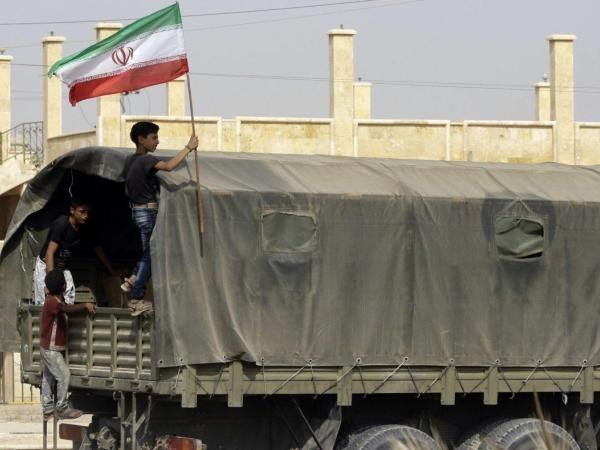 Một cậu bé Syria cầm cờ Iran đứng trên một chiếc xe tải chở hàng viện trợ do Tehran cung cấp cho Damascus