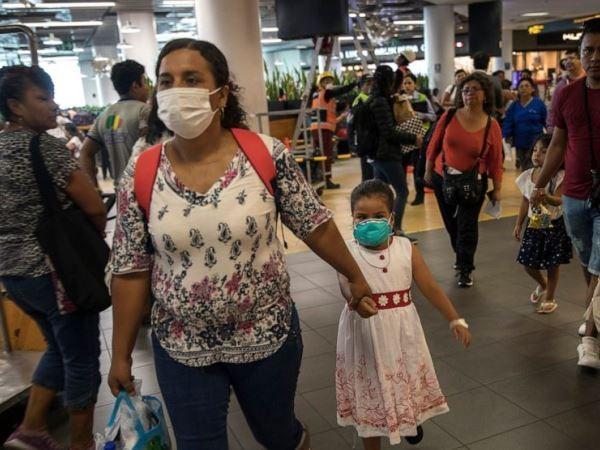 Hai mẹ con người Peru đeo khẩu trang đến phòng chờ khởi hành tại sân bay quốc tế ở Lima, Peru, ngày 6-3-2020