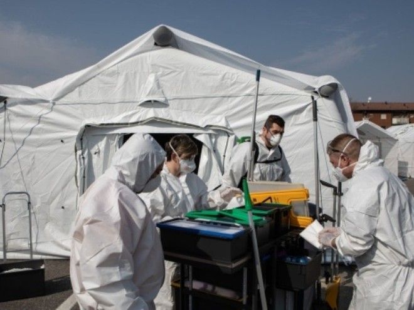 Nhân viên y tế trong bộ đồ bảo hộ đứng trước lều tại một bệnh viện dã chiến khẩn cấp ở Cremona, Italia, ngày 20-3-2020