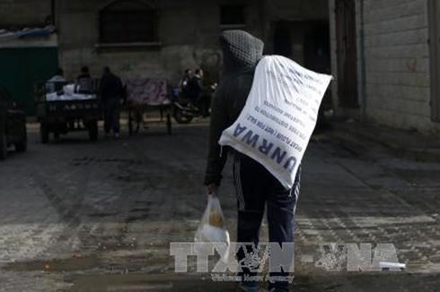 Người dân Palestine chuyển lương thực cứu trợ bên ngoài trung tâm phân phối lương thực của LHQ tại Gaza. (Ảnh: AFP/TTXVN)