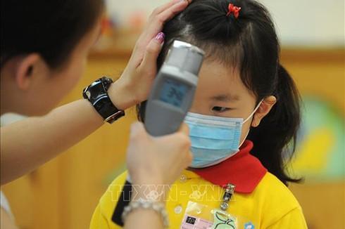 Kiểm tra thân nhiệt cho trẻ em tại một trường mầm non ở Hong Kong, Trung Quốc, để ngăn ngừa sự lây lan của dịch cúm. Ảnh: AFP/TTXVN