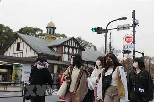 Người dân đeo khẩu trang phòng tránh lây nhiễm dịch COVID-19 tại Tokyo, Nhật Bản, ngày 25-2. (Ảnh: THX/TTXVN)