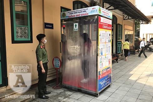 Công dân được khử khuẩn qua hệ thống buồng khử khuẩn di động được lắp đặt tại cổng ra vào của công an quận