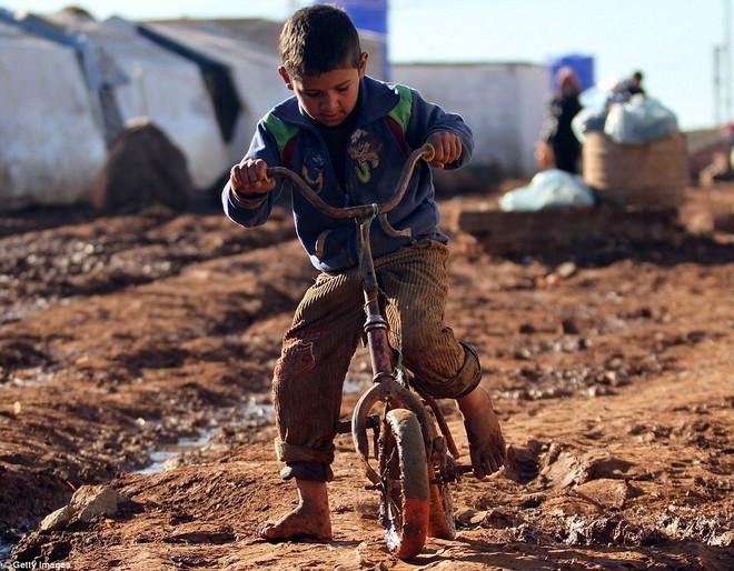 Một cậu bé vô tư chơi cùng một chiếc xe đạp hỏng trên con đường vào trại tị nạn Aleppo